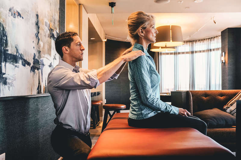 physical therapist evaluating a woman with poor posture and shoulder pain