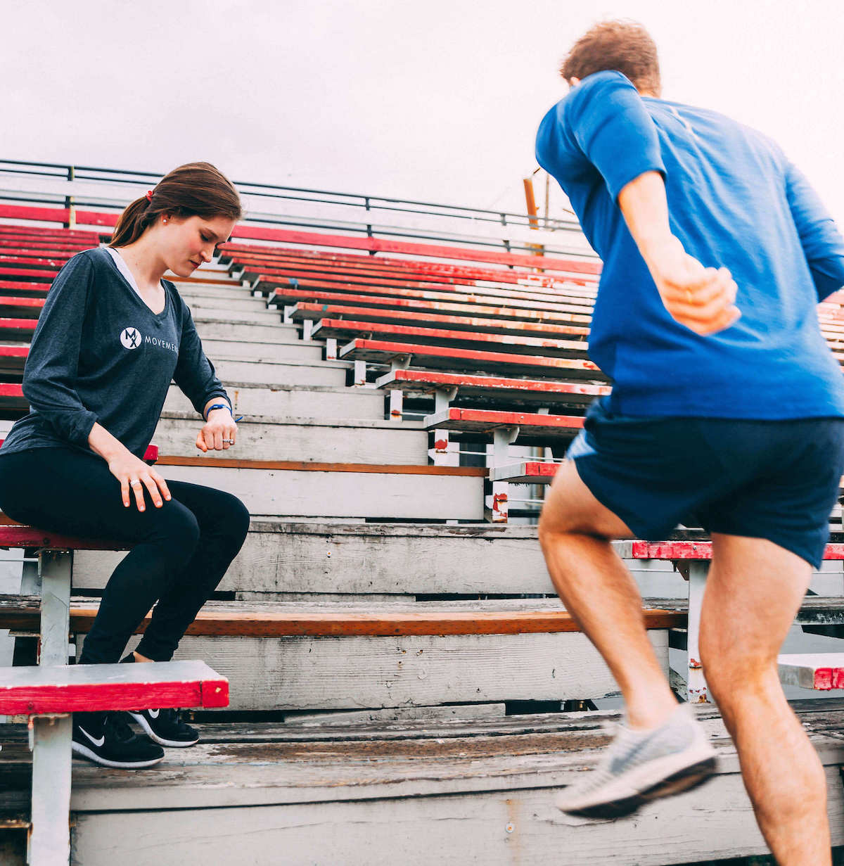 Man training and running with physical therapist on stairs