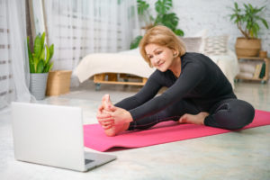 Woman stretching during physical therapy telehealth session
