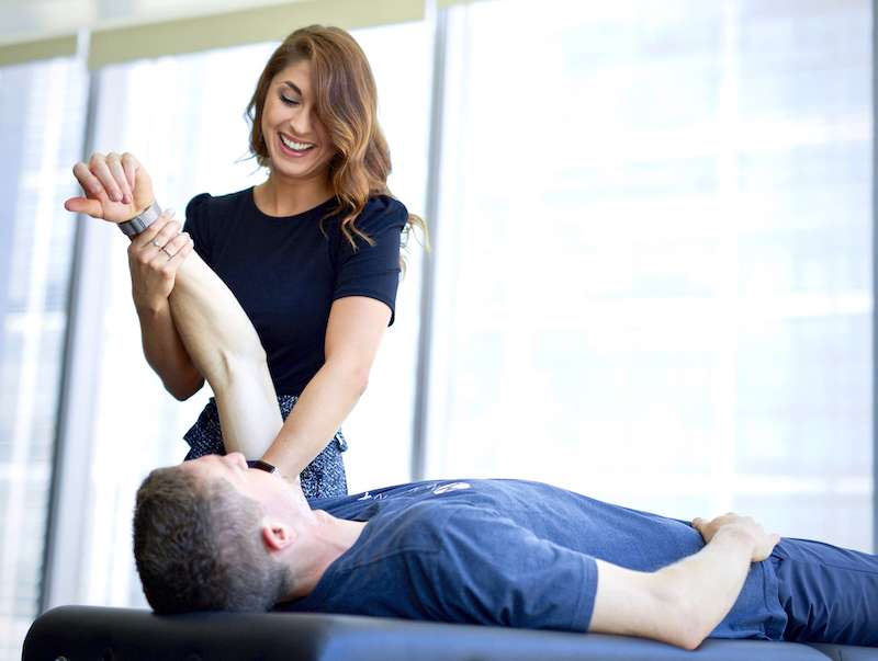Woman performing hands on treatment, manual therapy, to a man's shoulder