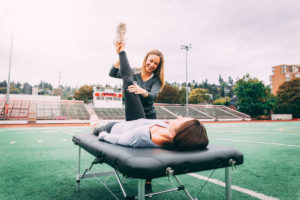 Physical therapist stretching a woman's hamstrings in Portland Oregon