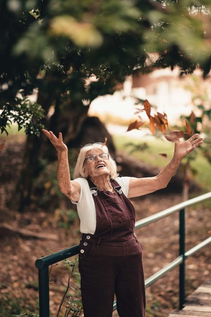Older woman with great balance throwing leaves without fallin