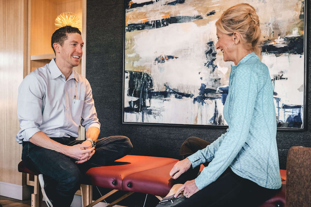 Male physical therapist talking with female patient in Arlington, Virginia