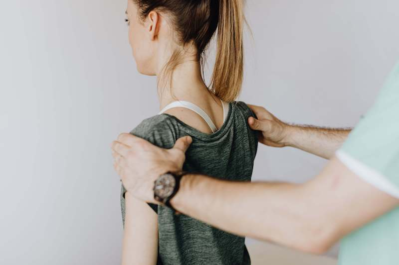 Physical therapist evaluating the posture of a woman with shoulder pain