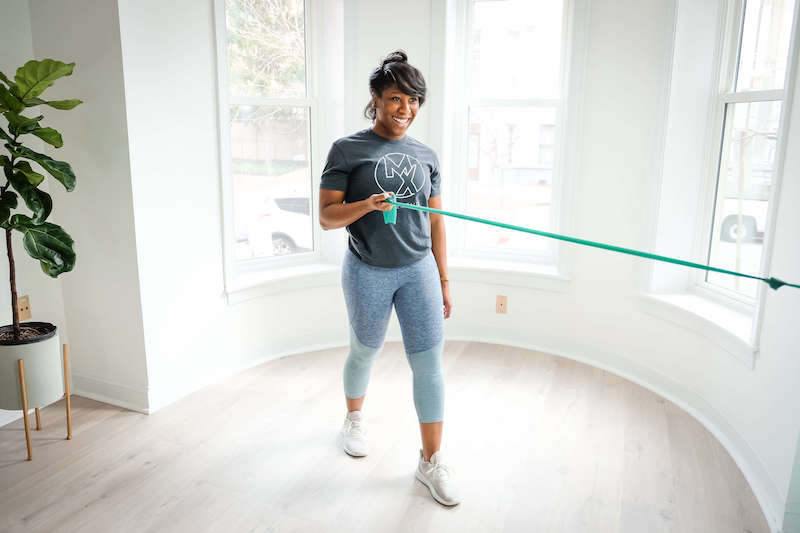Woman exercising with bands for her shoulder pain while at physical therapy