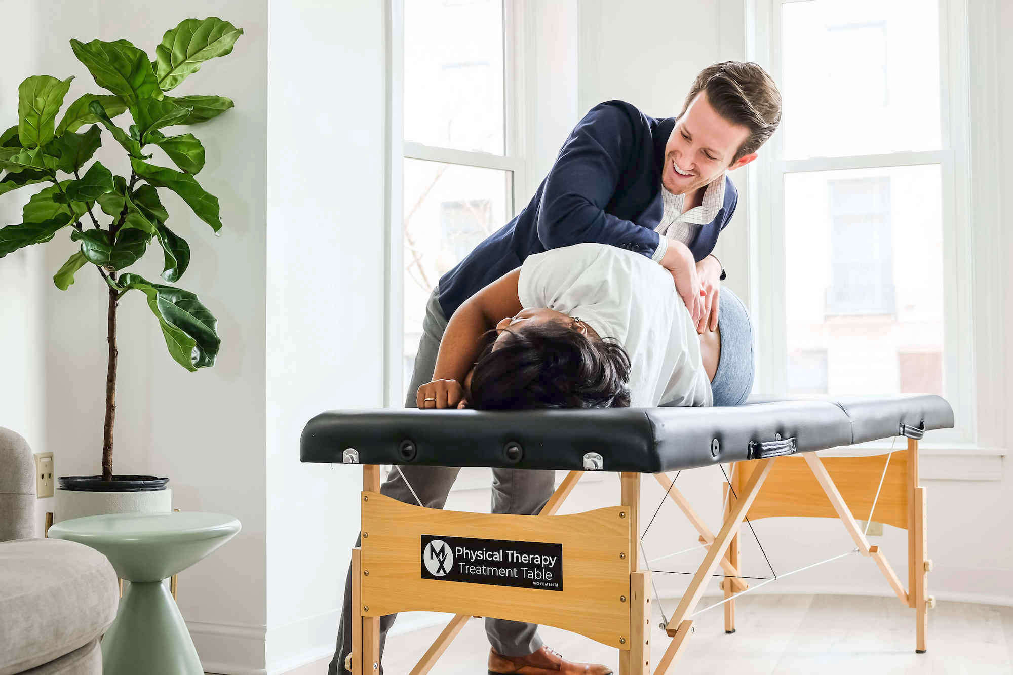 Physical therapist treating low back pain with an adjustment in Arlington, Virginia